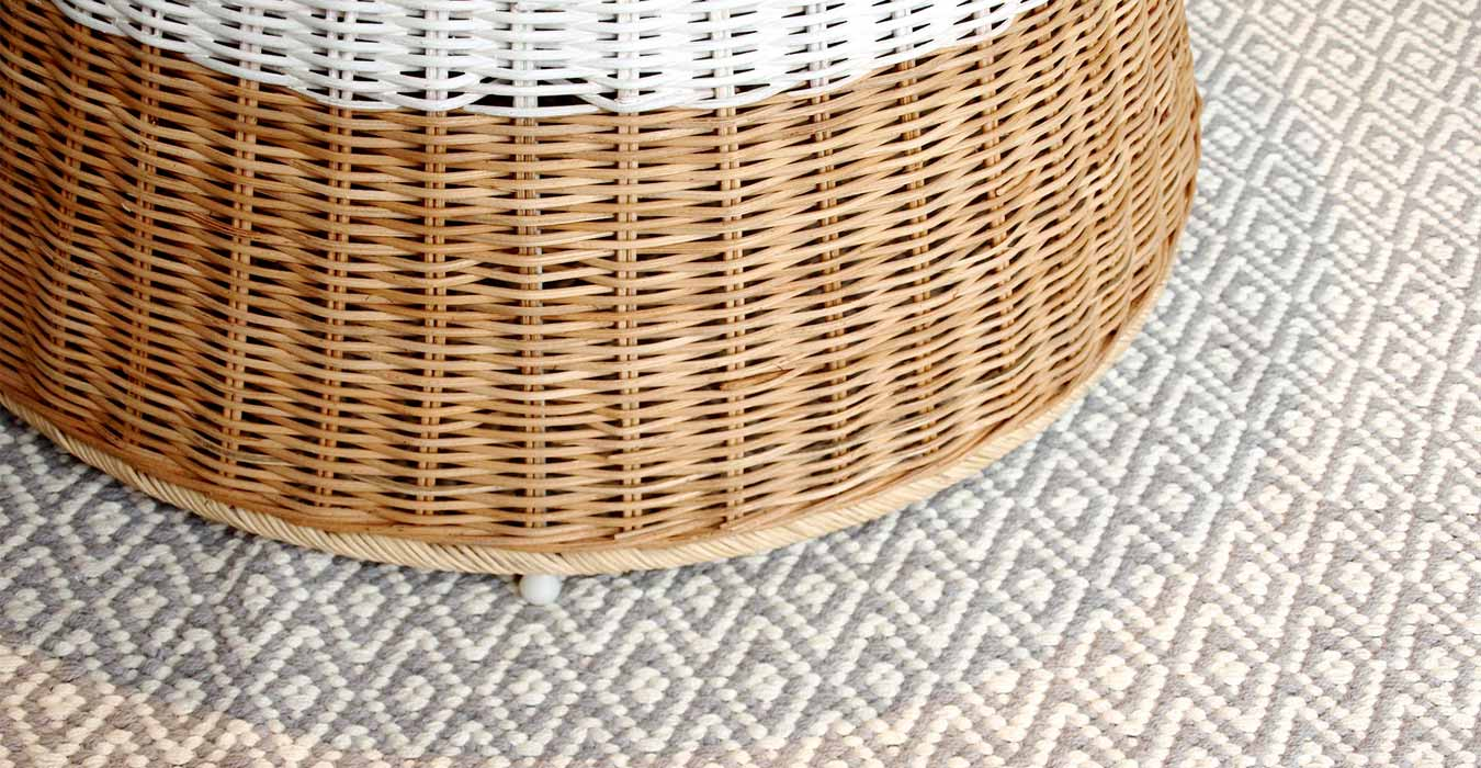 Wicker table on top of a cotton grey carpet